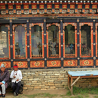 Asia, Bhutan, Thimpu. Three men sit on a bench at The Memorial Chorten in Thimpu.