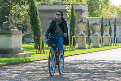 © Licensed to London News Pictures. 13/04/2014. London, UK. A woman cycles throughout the grounds. People enjoy the morning sunshine at Chiswick House in West London today 13th April 2014. Photo credit : Stephen Simpson/LNP