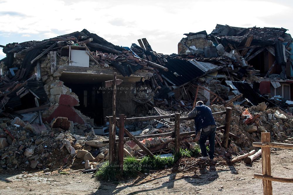 Un operaio di Italo-Argentino in una pausa dalla costruzione delle nuove abitazioni a Torrita, guarda le macerie.<br /> Sisma 2016