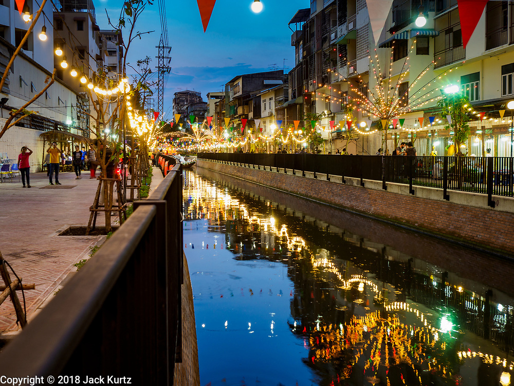 19 NOVEMBER 2018 - BANGKOK, THAILAND: Lights reflected in the canal during the Loy Krathong Fair along Klong (Canal) Ong Ang in Bangkok. This the first public event along the canal. Businesses that line the canal weve evicted about two years and the walkways along the canal were renovated. Loy Krathong takes place on the evening of the full moon of the 12th month in the traditional Thai lunar calendar. In the western calendar this usually falls in November. Loy means 'to float', while krathong refers to the usually lotus-shaped container which floats on the water. Traditional krathongs are made of the layers of the trunk of a banana tree or a spider lily plant. Now, many people use krathongs of baked bread which disintegrate in the water and feed the fish. A krathong is decorated with elaborately folded banana leaves, incense sticks, and a candle. A small coin is sometimes included as an offering to the river spirits. On the night of the full moon, Thais launch their krathong on a river, canal or a pond, making a wish as they do so. The krathongs made at the Klong Ong Ang fair were made out of bread so they would decompose and feed the fish in the canal. Loy Krathong will be celebrated on November 22 this year.    PHOTO BY JACK KURTZ