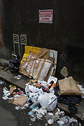 Illegally dumped rubbish beneath a sign warning of prosecution for fly-tipping violators, in a side-street off Oxford Street in the West End, on 16th January 2019, in London, England.