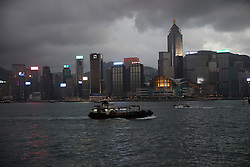 Hong Kong, China skyline with a stormy evening sky viewed across Victoria Harbor.