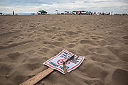 A - no swimming due to oil spill - sign is left broken and ignored in nearby Newport Beach. An estimated 127,000 gallons of crude oil leaked from an oil derrick pipeline in the Catalina Channel. The oil spread to nearby Huntington Beach beaches and wetlands, and quickly prompted cleanup crews to the scene. Orange County, California, USA