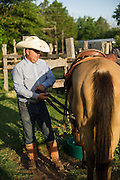 Rylan White saddles horses prior to the day's work at Island Ranch.