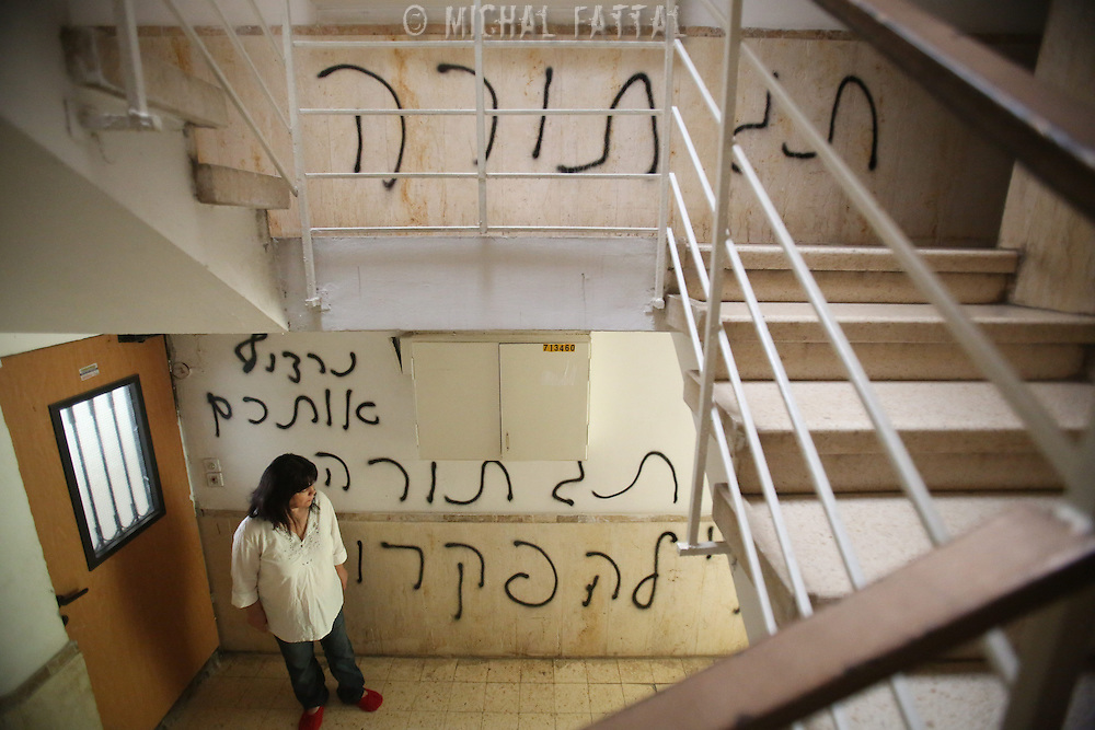 """Peggy Cidor, a leading woman of the Women of the Wall organization, stand in the hallway of her building in Jerusalem, Monday, May 20, 2013. The grafitti reads"""" The women of the Western Wall are despised"""". The group, known as """"Women of the Wall,"""" convenes monthly prayer services at the Western Wall, the holiest site where Jews can pray, wearing prayer shawls and performing rituals that ultra-Orthodox Jews believe only men are allowed to do...Israeli officials initially opposed the group but have recently backed its right to worship. Earlier this month, thousands of ultra-Orthodox protesters tried to prevent their prayer service."""