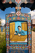 Tombstone of a carpenter, The  Merry Cemetery ( Cimitirul Vesel ),  Săpânţa, Maramares, Northern Transylvania, Romania.  The naive folk art style of the tombstones created by woodcarver  Stan Ioan Pătraş (1909 - 1977) who created in his lifetime over 700 colourfully painted wooden tombstones with small relief portrait carvings of the deceased or with scenes depicting them at work or play or surprisingly showing the violent accident that killed them. Each tombstone has an inscription about the person, sometimes a light hearted  limerick in Romanian. .<br /> <br /> Visit our ROMANIA HISTORIC PLACXES PHOTO COLLECTIONS for more photos to download or buy as wall art prints https://funkystock.photoshelter.com/gallery-collection/Pictures-Images-of-Romania-Photos-of-Romanian-Historic-Landmark-Sites/C00001TITiQwAdS8