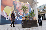 A billboard for jewellery retailer Vashi covers their Covent Garden exterior, behind signs urging Londoners to observe Covid social distance rules during the third lockdown of the Coronavirus pandemic, on 2nd February 2021, in London, England.