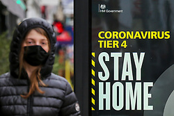 © Licensed to London News Pictures. 26/12/2020. London, UK. A woman wearing a face covering in north London walks past the government's 'Coronavirus Tier 4 - Stay Home' publicity campaign poster as many parts of the UK entered the highest level of COVID-19 restrictions on Boxing Day after mutated COVID-19 strains continue to spread around the country. Prime Minister, Boris Johnson refused to rule out a third national lockdown in the New Year. Photo credit: Dinendra Haria/LNP