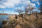 Tony Osborne and Vance Fielder look over decoy spread in front of duck blind on a private watershed lake in Shamrock, Oklahoma