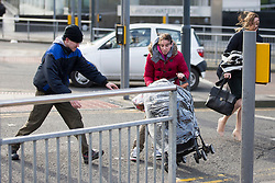 © Licensed to London News Pictures. 02/02/2016. Leeds UK. A woman struggles to keep hold of her child's buggie in todays high winds as she tried to cross a road at Bridgewater place in Leeds. Photo credit: Andrew McCaren/LNP