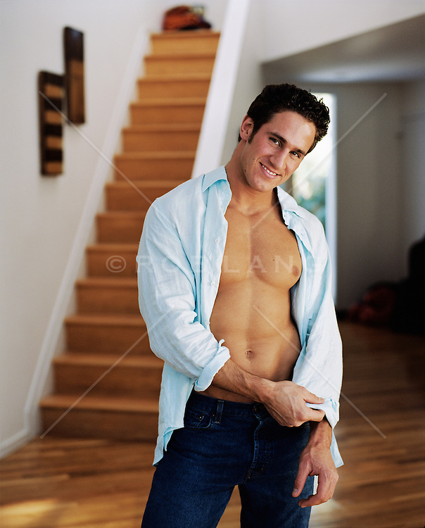 good looking man with open shirt at home