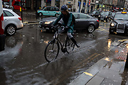 A cyclist splashes through rain water as Storm Georgina swept across parts of Britain and in central London, lunchtime office workers were caught out by torrential rain and high winds, on 24th January 2018, in London, England. Pedestrians resorted to leaping across deep puddles at the junction of New Oxford Street and Kingsway at Holborn, the result of overflowing drains.