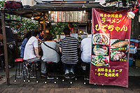 """A yatai is a small, mobile food stall typically selling ramen, yakitori or oden. The name literally means """"shop stand."""" The stall is set up in the early evening on sidewalks and removed late at night or in the early morning hours. Beer, sake and shochu are usually available. A salaryman might relax with colleagues over dinner and drinks at a yatai on his way home from work. Fukuoka is well known in Japan for keeping the yatai tradition alive."""