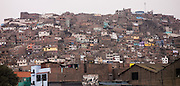 Houses stack up tightly onto a hill in Lima, Peru, South America.