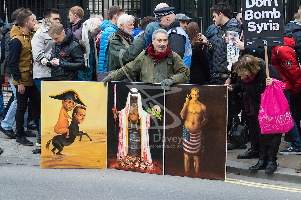 London, November 28th 2015. As Prime Minister David Cameron pushes for Parliament to vote to allow aerial strikes against Islamic State targets in Syria, Britain's Stop The War Coalition and thousands of anti-war protesters demonstrate outside Downing Street. PICTURED: Satirical painter Kaya Mar displays his paintings.  //// FOR LICENCING CONTACT: paul@pauldaveycreative.co.uk TEL:+44 (0) 7966 016 296 or +44 (0) 20 8969 6875. ©2015 Paul R Davey. All rights reserved.