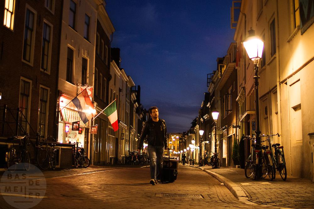Een man loopt 's avonds met bagage door de Lange Smeestraat in Utrecht.<br /> <br /> A man is walking with his luggage late in the evening in de Lange Smeestraat in Utrecht