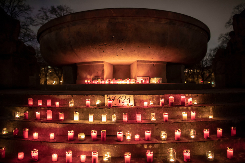 """Candles burn at a makeshift memorial in Berlin, Germany, January 17,  2021. The memorial is part of the initiative  """"Corona-Tote sichtbar machen"""" (lit. Make corona deaths visible) by Christian Y. Schmidt and Veronika Radulovic,  since December 6, 2020, people gather at the fountain of Arnswalder Platz every Sunday at 16:00, light candles and place placards with the current death toll reported in Germany at the time. The death toll in Germany by variouse sources revolved around 47,000."""