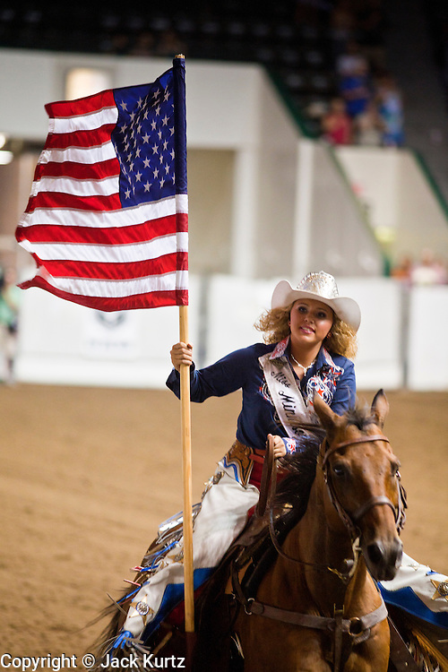 """01 SEPTEMBER 2011 - ST. PAUL, MN:  A woman on horseback carries the American flag around the arena at the opening of a high school rodeo performance at the Minnesota State Fair. The Minnesota State Fair is one of the largest state fairs in the United States. It's called """"the Great Minnesota Get Together"""" and includes numerous agricultural exhibits, a vast midway with rides and games, horse shows and rodeos. Nearly two million people a year visit the fair, which is located in St. Paul. PHOTO BY JACK KURTZ"""