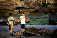 Indonesia, Bali. Two balinese boys playing with a kite in Tanah Lot.