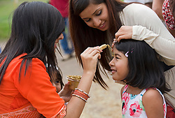 CAPTION CORRECTION...© Licensed to London News Pictures. 21/08/2011. Aldenham, UK. A young girl receives a Talik mark on her forehead at Bhaktivedanta Manor Temple near Watford today (21/08/2011) to celebrate  the festival of Janmashtami, a celebration of the birth anniversary of Lord Krishna. Janmashtami at Bhaktivedanta Manor is the largest Krishna gathering outside of India with over 60,000 people attending over two days. Bhaktivedanta Manor was donated to the Hare Krishna movement in the early 1970's by former Beatle George Harrison. Photo credit: Ben Cawthra/LNP