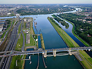 Nederland, Zuid-Holland, Rotterdam, 14-09-2019; Haven van Rotterdam, Botlek, Hartelkanaal met Hartelkering (stormvloedkering) tijdens de jaarlijkse Functioneringssluiting. <br /> De kering, onderdeel van de Deltawerken, vormt samen met de Maeslantkering de Europoortkering en beschermt Rotterdam en achterland bij extreme waterstanden. De keringen worden een maal per jaar, voordat het stormseizoen begint, getest. Tijdens het sluiten van de kering ligt alle scheepvaartverkeer naar de Rotterdamse haven stil. In de achtergrond Botlekbrug en Shell-olieraffinaderij, Hoogvliet.<br /> Aerial view of one of the two storm surge barriers. This barrier, the Hartelkering in the Hartel canal, together with the greater nearby Maeslant barrier (in the New Waterway), are tested during the so-called functioning closure, taking place one a year before the storm season begins. The waterway and canal, leading to the Port of Rotterdam, are closed during the test.<br /> <br /> luchtfoto (toeslag op standard tarieven);<br /> aerial photo (additional fee required);<br /> copyright foto/photo Siebe Swart