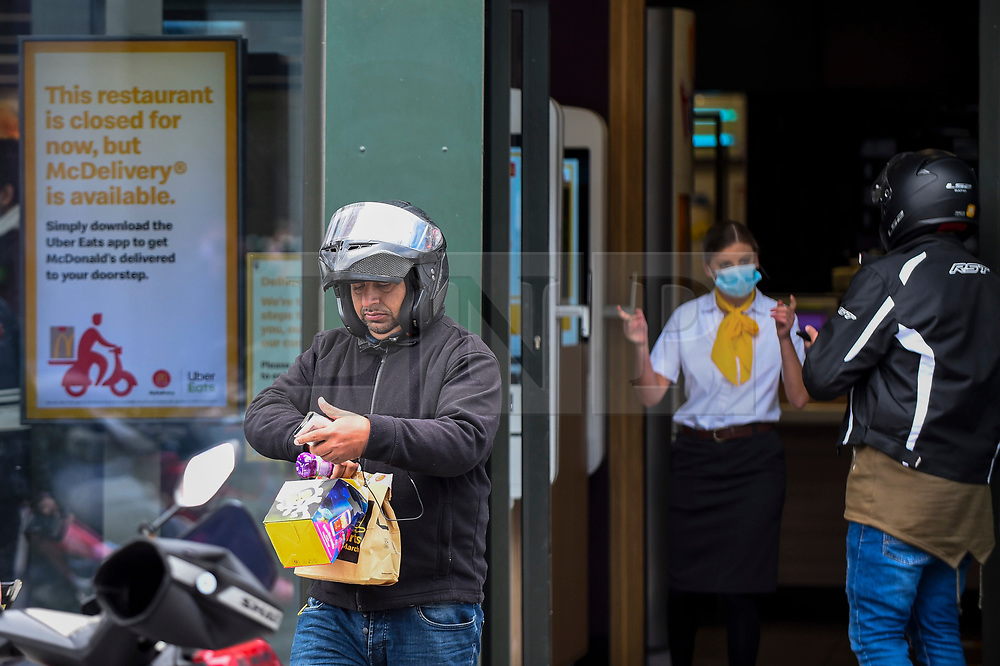 """© Licensed to London News Pictures. 13/05/2020. LONDON, UK. A delivery rider carries an order as the McDonald's fast food restaurant in Harrow reopens for """"McDelivery"""" during the ongoing coronavirus pandemic.  The restaurant is one of 14 in the UK that the chain is partially reopening with a limited menu and delivery only.  Delivery is satisfied by third parties such as Uber Eats and Deliveroo.  Photo credit: Stephen Chung/LNP"""