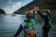 """Baton crosses Pasay bay on a boat on the 20th Korrika.  Pasaia (Basque Country). April 4, 2017. The """"Korrika"""" is a relay course, with a wooden baton that passes from hand to hand without interruption, organised every two years in a bid to promote the basque language. The Korrika runs over 11 days and 10 nights, crossing many Basque villages and cities. This year was the 20th edition and run more than 2500 Kilometres. Some people consider it an honour to carry the baton with the symbol of the Basques, """"buying"""" kilometres to support Basque language teaching. (Gari Garaialde / Bostok Photo)"""