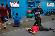 Strength coach Adrian Ramirez stretches Johny Hendricks before training at Velociti Fitness while the rest of the team watches his upcoming opponent Robbie Lawler on the television in Pantego, Texas on February 6, 2014.