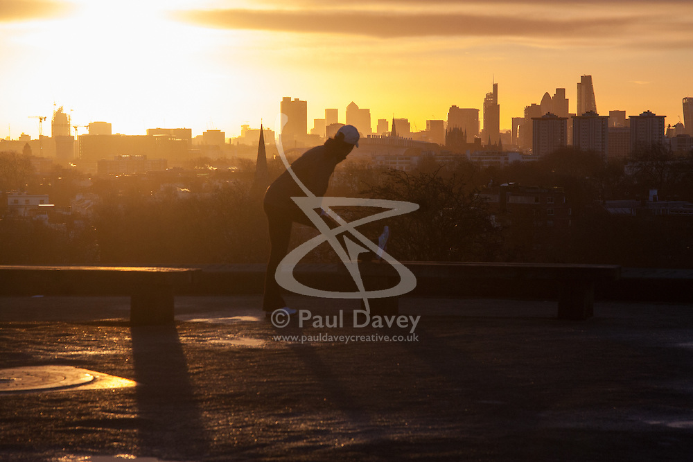 Primrose Hill, London, March 2nd 2015. As forecasters are beginning to predict the coming of spring, the sun rises over London as dog walkers and runners exercise on Primrose Hill as the sun rises on a chilly London morning. PICTURED: Management consultant Jacqui Rowlands exercises as the sun rises over London.