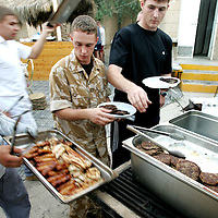 Baghdad, Iraq, 2 Oct 2005. Running 'Route Irish'...Members of the Signals unit at a base barbeque.....B Company, 1st Battalion, The Royal Irish Regiment, a tight-knit multi national fighting force make daily escorting runs along ?Route Irish?, the infamous Baghdad Airport road. The 46 man team are all British Army regulars but come from as far afield as Fiji, South Africa and Northern and Southern Ireland. Previous deployments in Kosovo, Sierra Leone and Northern Ireland have equipped them with the valuable skills needed to provide protection for British Forces and materials transiting the world?s most dangerous highway. Due to an increased presence of US forces along the route both in dug in positions and mobile patrols, attacks along the road have slackened, despite this a day rarely passed without an IED (improvised explosive device) being detonated or a small arms attack against coalition forces. ..The convoy attempts to maintain a seclusion ?bubble? around its vehicles for the duration of the journey. Any civilian vehicle that either strays into the bubble or refuses to keep their distance represents a threat and should they ignore the warning blasts on air horns carried in each vehicle the rules of engagement progress from warning shots to use of lethal force. The relative safety of the International Zone offers them an opportunity to decompress between missions. A duty driver ferries soldiers to the ?Liberty Pool?. Once only frequented by Iraq?s Ba?athist elite the luxury swimming pool and gym now fills with troops. Their body armour, helmets and weapons all within easy reach they either soak up the sun or compete with each other in diving competitions. After a daily briefing the troops have access to the ?Mosquito and Camel? bar where they watch TV or play pool and in accordance with the ?2 can rule? are allowed to drink 2 beers per night.