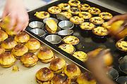 """Two ladies remove a batch of """"pastéis de Belém"""" form moulds to cool them."""