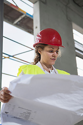 Female architect reviewing blueprint at construction site, Munich, Bavaria, Germany
