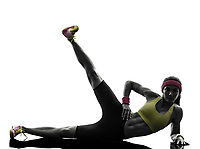 one woman exercising fitness workout legs in the air lying on side in silhouette on white background