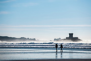 Silhouette of a couple walking by the shoreline in front of la Rocco Tower at St Ouen's Bay, Jersey, CI on a sunny, but cold winter day