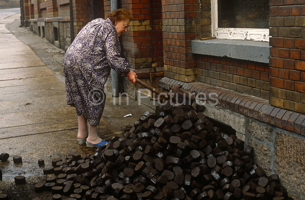 Six months after the fall of the Berlin Wall, a lady shovels East German Lignite coal briketts left outside her home, on 1st June 1990, in Aue, Saxony, eastern Germany former DDR. The coal was delivered as Briketts and was either Lignite or Braunkohle, imported from either Poland or northern Czech Republic.