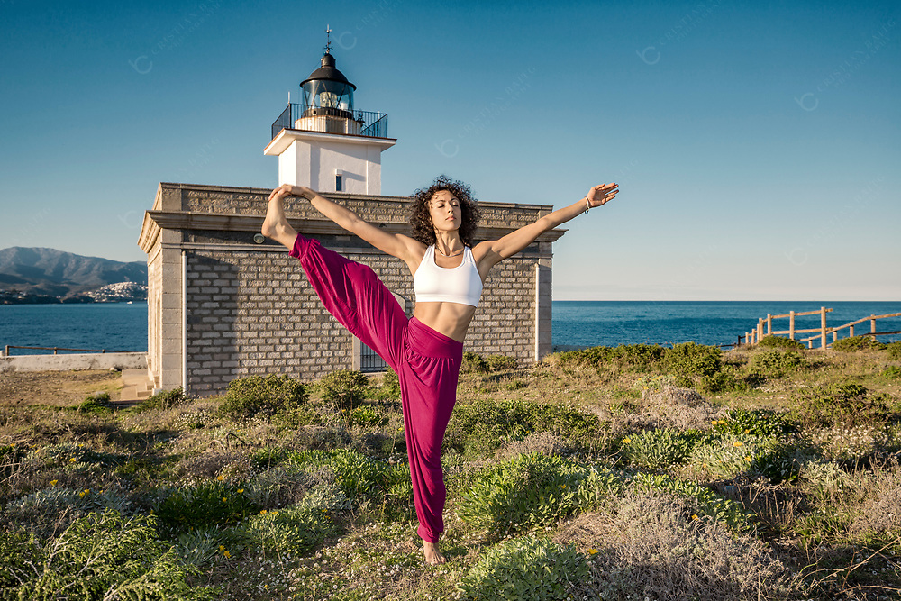Woman doing Extended Hand To Big Toe yoga pose at the sea