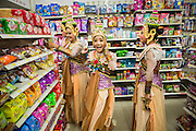 08 APRIL 2013 - CHIANG MAI, CHIANG MAI, THAILAND: Girls in tradition Thai costumes buy snacks in a convenience store before performing at a Songkran pageant in Chiang Mai, Thailand. Songkran is celebrated in Thailand as the traditional New Year's Day from 13 to 16 April. Songkran is in the hottest time of the year in Thailand, at the end of the dry season and provides an excuse for people to cool off in friendly water fights that take place throughout the country. The traditional Thai New Year has been a national holiday since 1940, when Thailand moved the first day of the year to January 1. The first day of the holiday period is generally the most devout and many people go to temples to make merit and offer prayers for the new year.   PHOTO BY JACK KURTZ