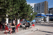 Lunchtime people enjoy autumn sunshine outside the new Pret a Manger cafe with the soon to be demolished Shopping Centre (right) at Elephant & Castle, south London.