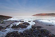 Low angle view on the beach near to Porlock Weir on the Bristol Channel coast, looking along a small rivulet in the sand towards Bossington Hill.