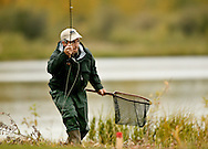 © 2007 Randy Vanderveen, all rights reserved.Kakut Pond, Worsley, Alberta.Sorin Comsa keeps low to remain out of sight of the trout in his area as he moves to another position while continuing to work his fly.  Anglers cast out their lines at Kakut Pond during the FFC National Fly Fishing Championships.