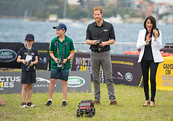 The Duke of Sussex drives a remote control car as the Duchess of Sussex looks on as they attend the Invictus Games Jaguar Land Rover Driving Challenge, on Cockatoo Island, Sydney, on the fifth day of the royal couple's visit to Australia.