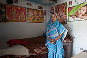 A young India girl sat in her one room dwelling.  She lives alone in a suburb of Delhi, India.