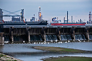 ships in the Mississippi River passing the Spillway in Norco, Dow chemical plant behind them.