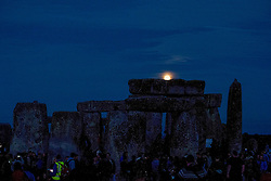 © Licensed to London News Pictures. 20/06/2016. STONEHENGE, WILTSHIRE, UK.  The full moon rises over Stonehenge on Summer Solstice, the first time since 1967. The next full moon at Summer Solstice is in 90 years.<br /> Summer solstice at the ancient stone circle at Stonehenge World Heritage site in Wiltshire..  Photo credit: MARK HEMSWORTH/LNP