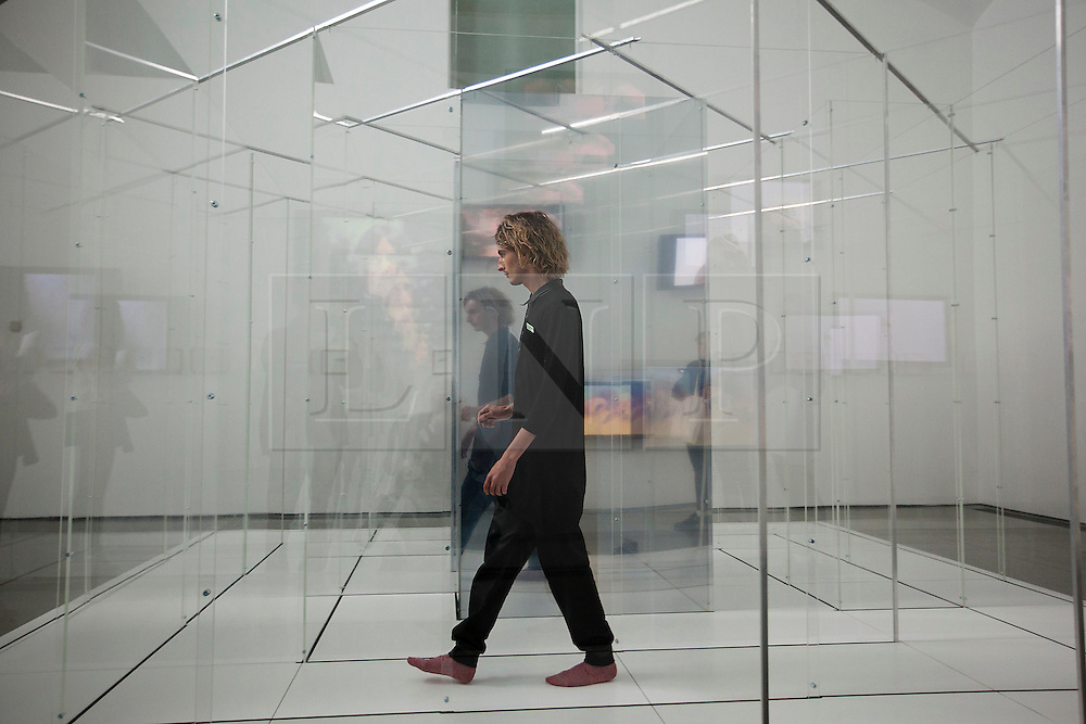 © Licensed to London News Pictures. 18/06/2012. LONDON, UK. A member of gallery staff walks through Yoko Ono's 'AMAZE' (1971/2012) at Serpentine Gallery in London today (18/06/12). The exhibition, entitled 'To The Light', is the artists first London based exhibition in more than a decade, including pieces featuring her late husband John Lennon and is set to run from 19th of June to 9th of September 2012. Photo credit: Matt Cetti-Roberts/LNP