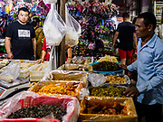 """14 FEBRUARY 2019 - SIHANOUKVILLE, CAMBODIA: A Chinese worker buys tofu from a Chinese market vender in the Leu Market in Sihanoukville. There are about 80 Chinese casinos and resort hotels open in Sihanoukville and dozens more under construction. The casinos are changing the city, once a sleepy port on Southeast Asia's """"backpacker trail"""" into a booming city. The change is coming with a cost though. Many Cambodian residents of Sihanoukville  have lost their homes to make way for the casinos and the jobs are going to Chinese workers, brought in to build casinos and work in the casinos.      PHOTO BY JACK KURTZ"""