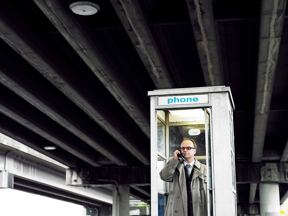 50's something man talking in pay phone booth under a freeway.