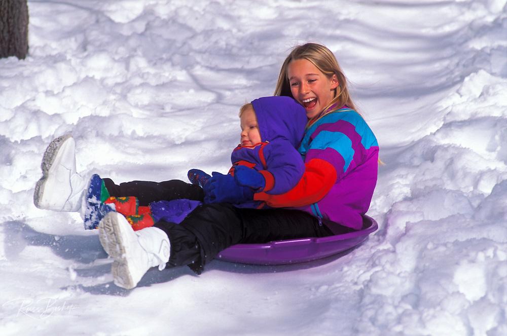 Kids (ages 2 & 10) riding a snow dish, San Berna5dino Mountains, California