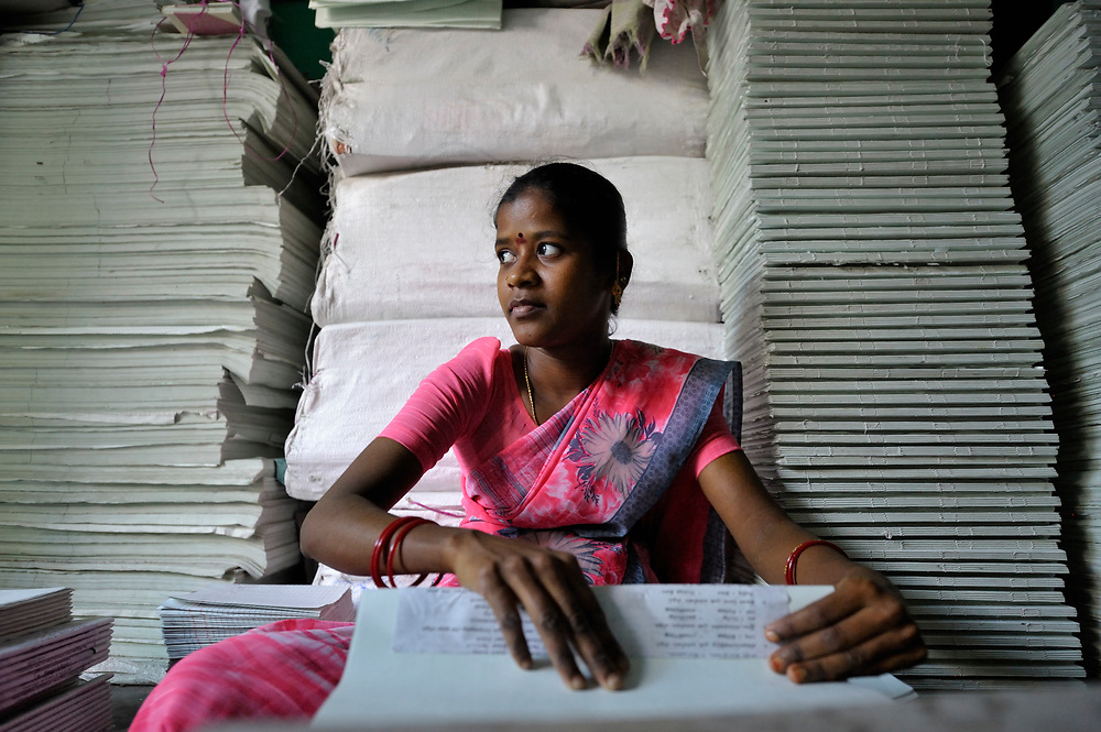 Manipandi assembles accounting books at a bookbinding shop in Madurai, a city in Tamil Nadu state in southern India. The business is owned and run by a woman who is a member of a self-help group.