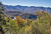 """At Plott Balsam Overlook on the Blue Ridge Parkway (Milepost 457.9, elevation 5020 ft), view fall foliage colors in mid October, in North Carolina, USA. The bend in US Highway 19 seen below turns down from Soco Gap and descends to Cherokee. The sign at Plott Balsam Overlook reads: """"Before you lies the massive Plott Balsam Range. On one of its eastern slopes Henry Plott, a German immigrant's son, made his home in the early 1800s. In this game-filled frontier, hunting dogs were a prized possesion. Here Henry Plott and his descendants developed the famous Plott Bear Hounds carefully selecting for the qualities of stamina, courage, and alertness the breed possesses today."""" North Carolina's state dog is the the Plott Hound. The 469-mile Blue Ridge Parkway was built 1935-1987 to aesthetically connect Shenandoah National Park (in Virginia) with Great Smoky Mountains National Park in North Carolina. (The Smokies are a subrange of the Blue Ridge Mountains, part of the Appalachian Mountains.)"""